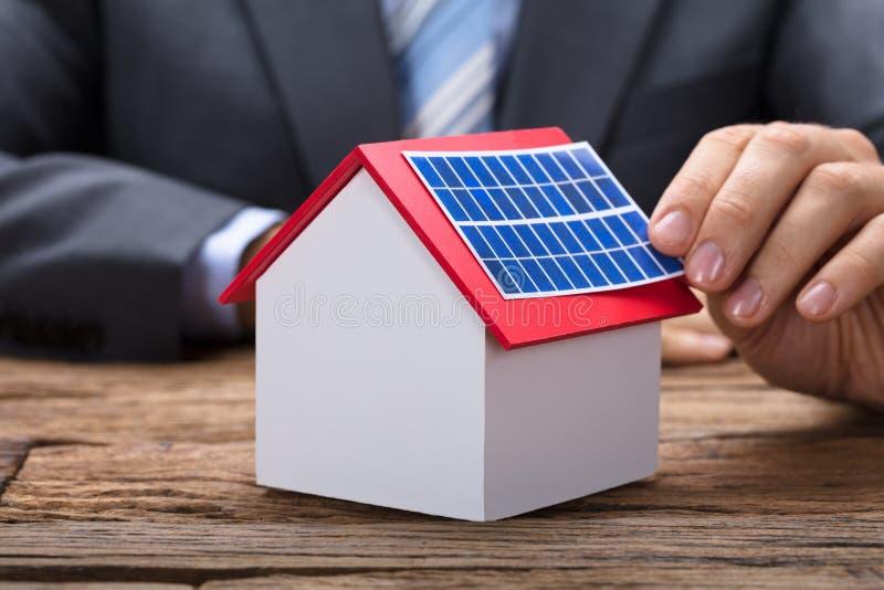 Businessman Sticking Solar Panel On Model Home stock photo