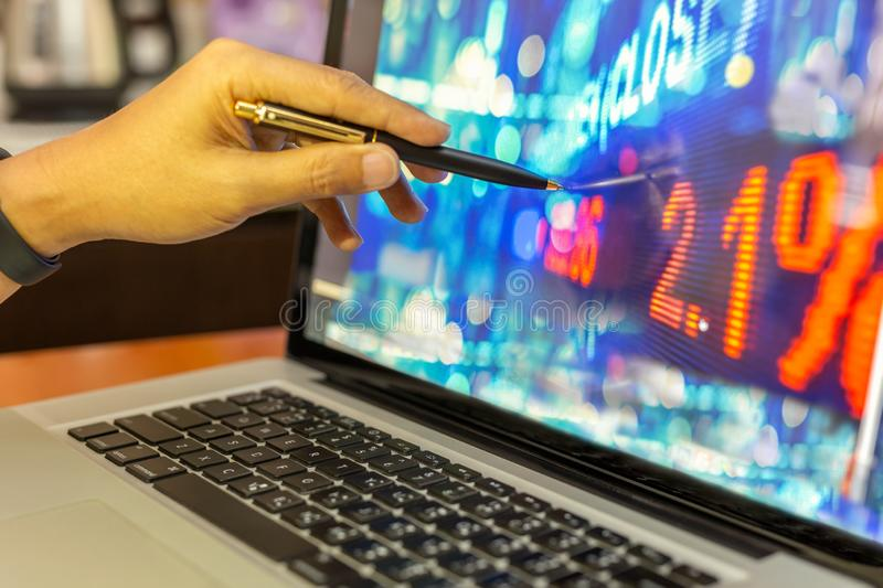 Businessman stock analysis hand with pen pointing on laptop screen financial chart graph in background. royalty free stock images