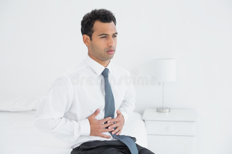 Businessman with stomach pain sitting on bed royalty free stock photos