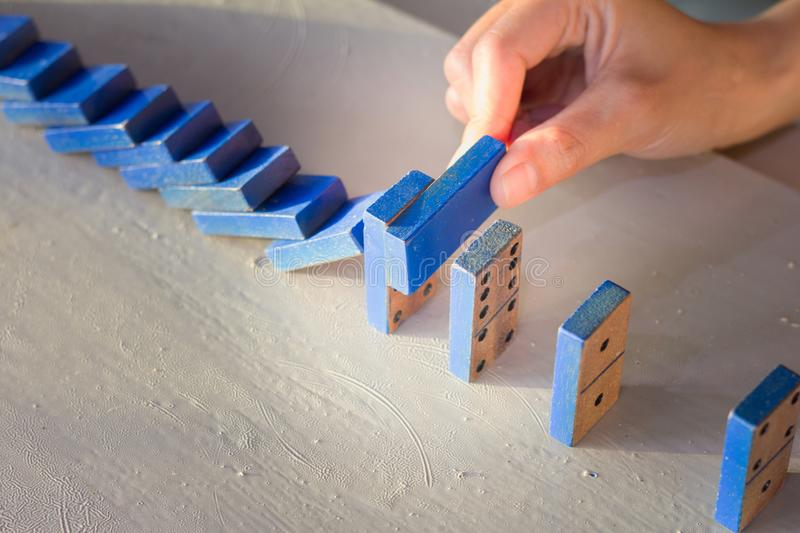 Businessman stop domino effect. Risk management concept royalty free stock images