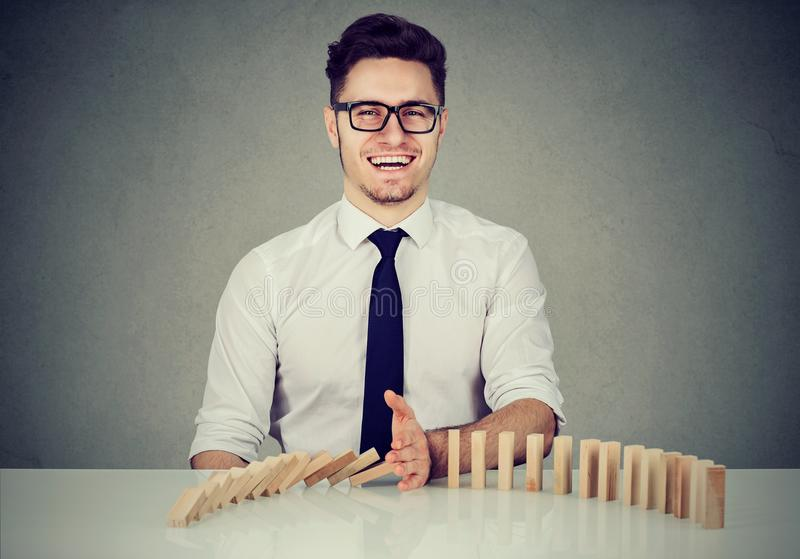 Businessman stopping the domino effect stock image