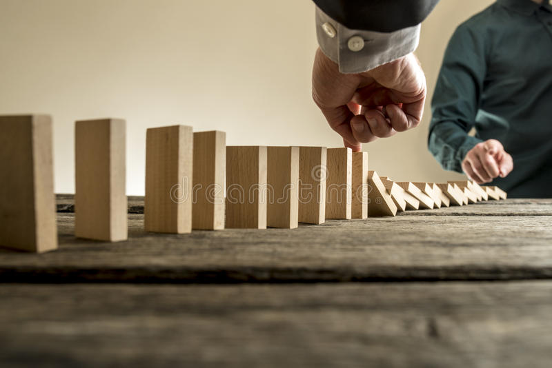 Businessman stopping the domino effect royalty free stock photography