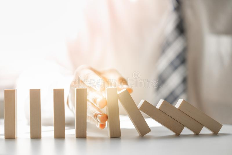 Businessman stopping domino effect represent to business crisis and risk management stock images