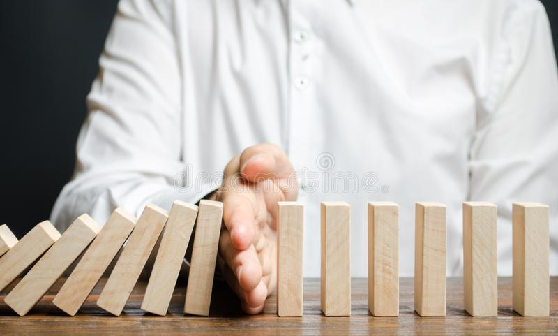 Businessman stops domino falling. Risk management concept. Successful strong business and problem solving. Reliable leader. Stop stock photo