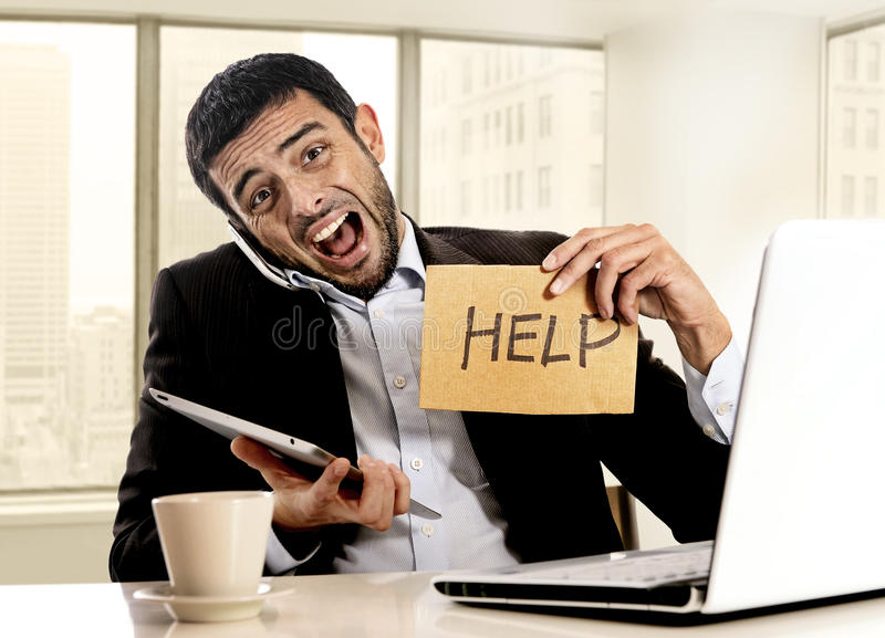 Businessman in stress holding help sign multitasking overwhelmed in business district office stock photo