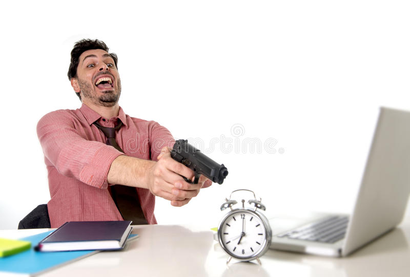 Businessman in stress at office computer desk pointing hand gun to alarm clock in out of time and project deadline expiring stock photo