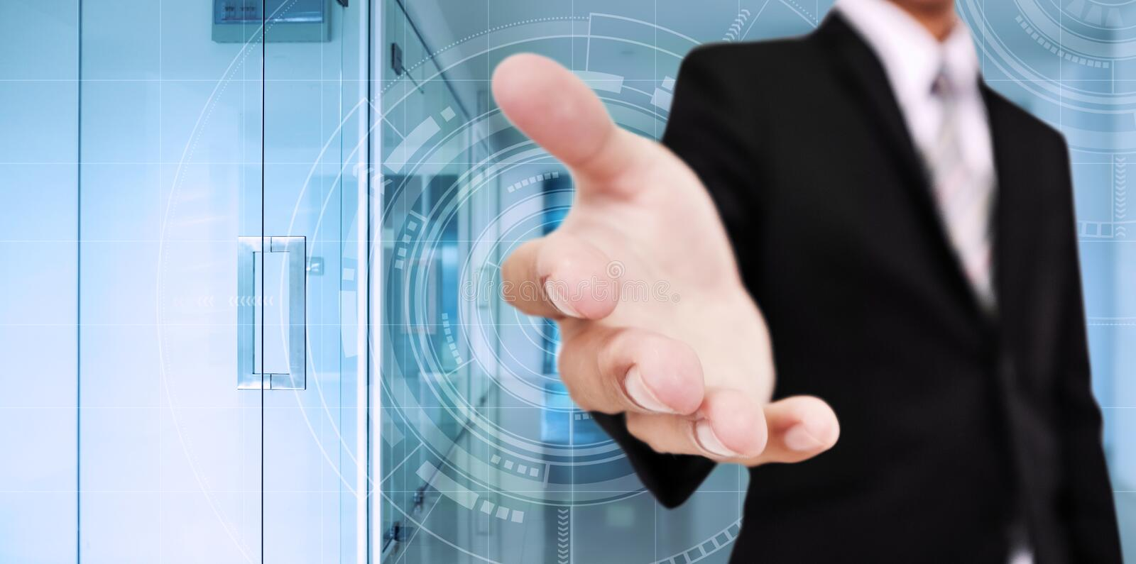 Businessman stretch out hand, with digital interface technology, with interior modern office background. S stock photo