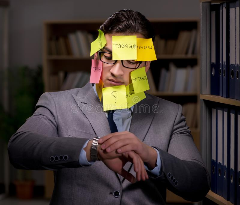 Businessman struggling with conflicting priorities during long h. Ours stock photo