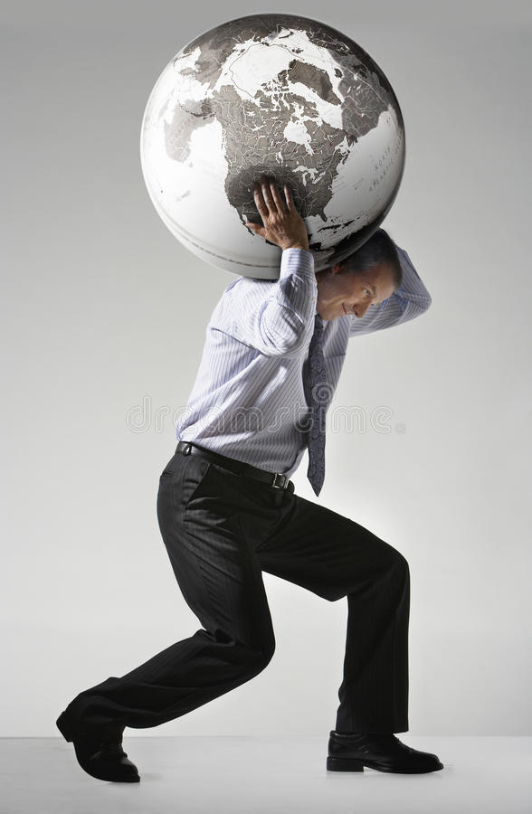Businessman Struggling To Carry Globe On Shoulders. Full length side view of a businessman struggling to carry globe on shoulders against gray background royalty free stock photo
