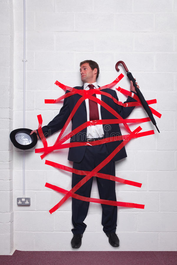 Businessman stuck to wall with red tape. Businessman holding an umbrella and bowler hat stuck to a wall with red tape stock image