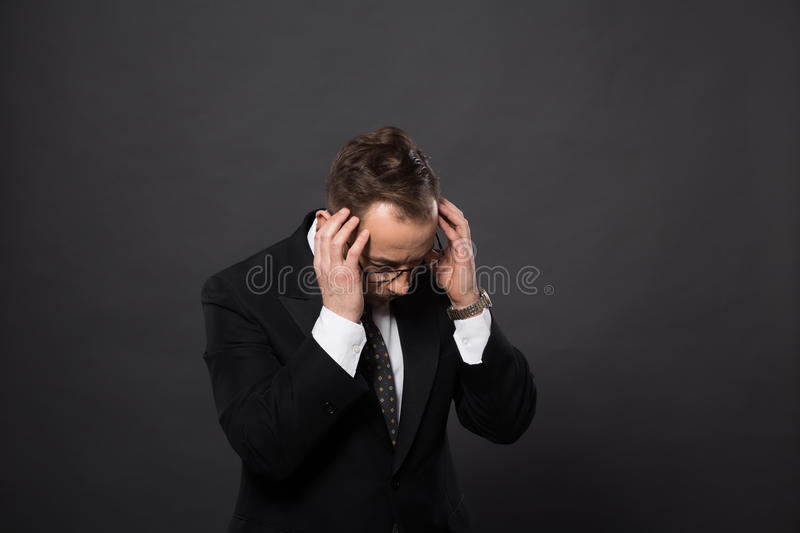 Businessman in studio. Businessman having headache after hard-working day in office. Studio shot of astonished and sad man in studio royalty free stock photography