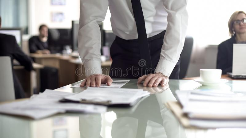 Businessman studying contract, office employees working on background, busy life. Stock photo royalty free stock images