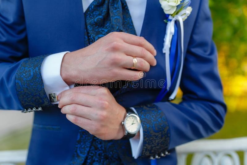 Businessman in a stylish blue suit with patterns adjusts the cuffs of his shirt. Stylish man in an expensive suit and tie and stock images