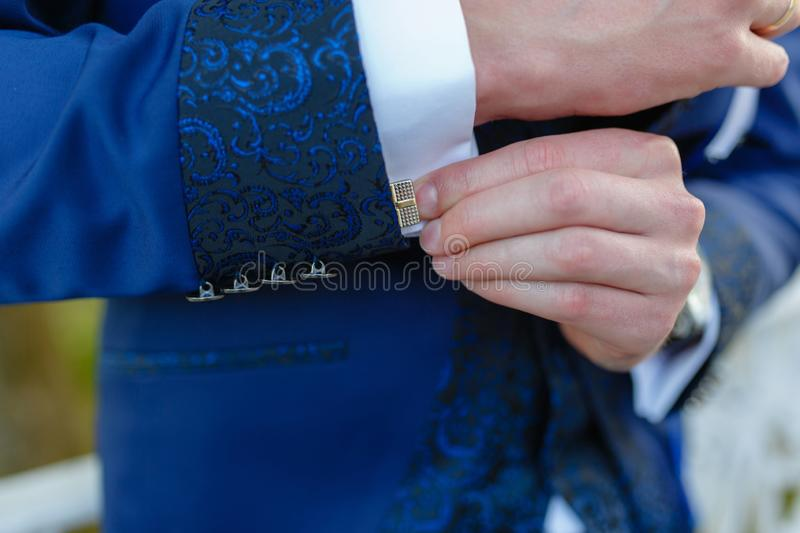 Businessman in a stylish blue suit with patterns adjusts the cuffs of his shirt. Stylish man in an expensive suit and tie and royalty free stock photo