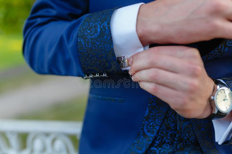 Businessman in a stylish blue suit with patterns adjusts the cuffs of his shirt. Stylish man in an expensive suit and tie and royalty free stock images