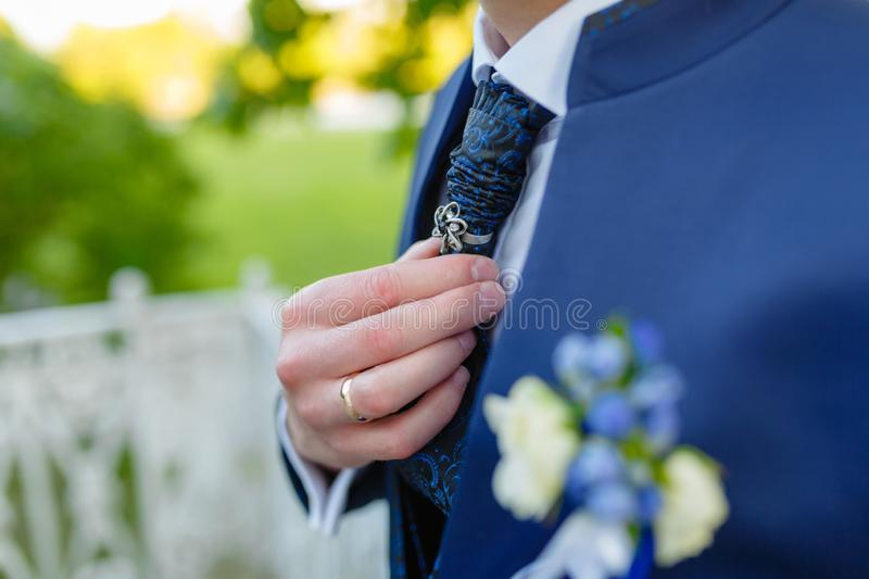 Businessman in a stylish blue suit with patterns straightens tie. Stylish man in an expensive suit and tie and jacket, close-up. stock photo