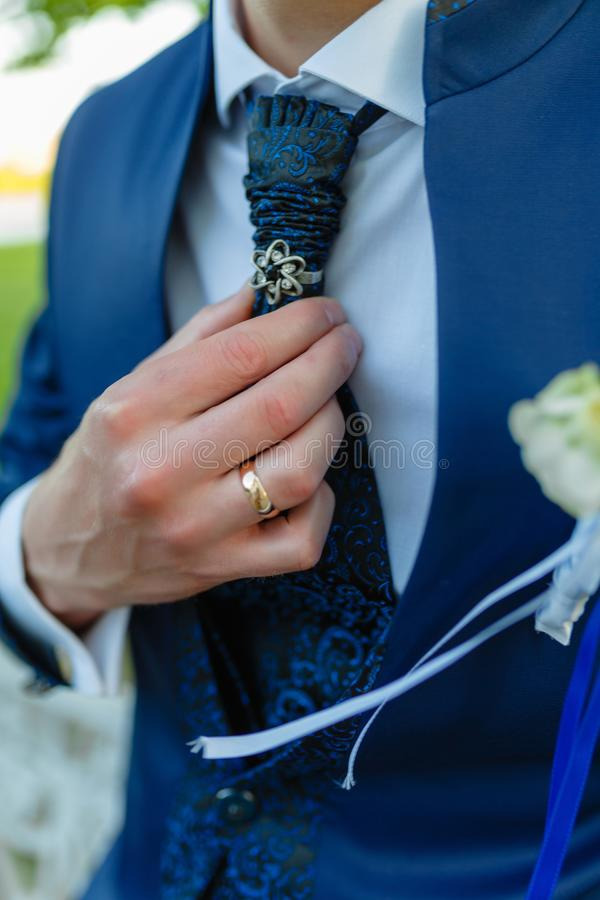 Businessman in a stylish blue suit with patterns straightens tie. Stylish man in an expensive suit and tie and jacket, close-up. stock images