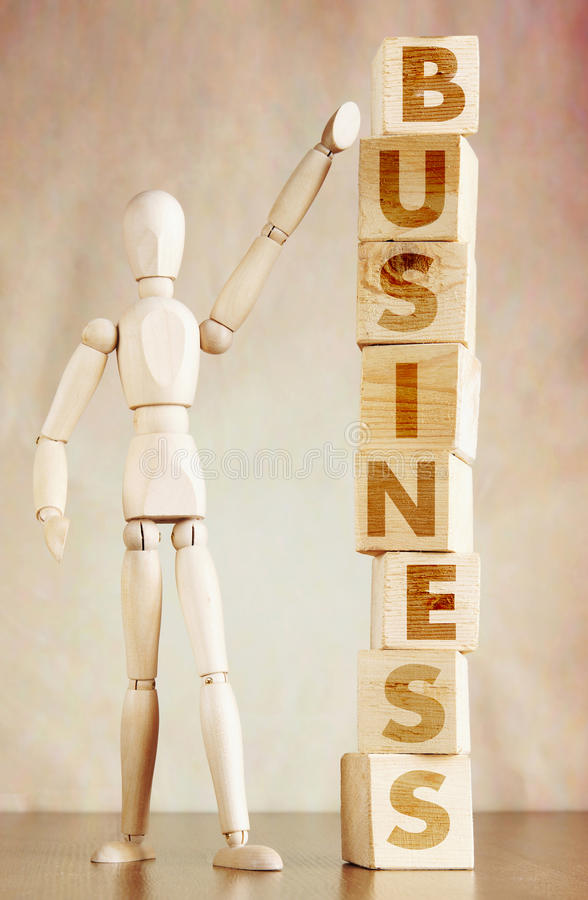 Businessman successfully builds his own business. Conceptual image with wooden puppet stock images