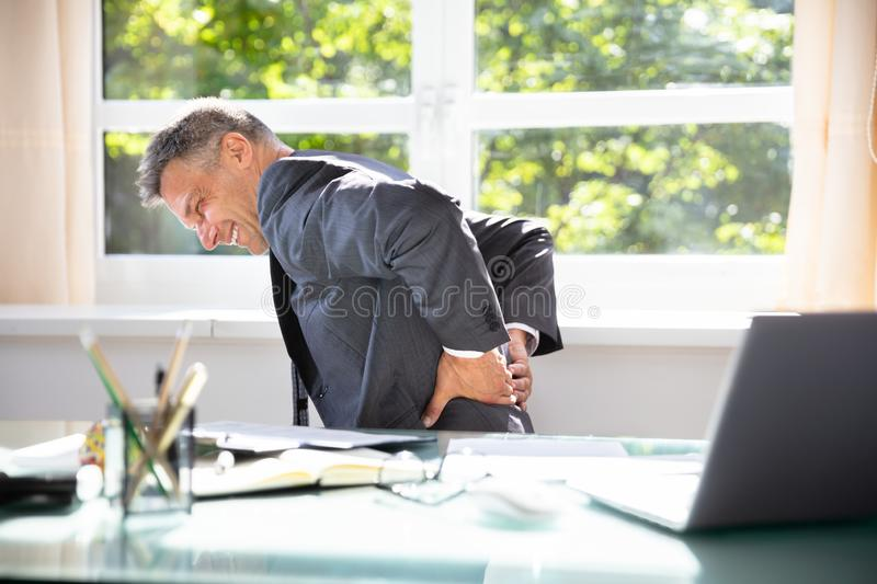Businessman Suffering From Back Pain. Side View Of A Mature Businessman Suffering From Back Pain In Office stock image
