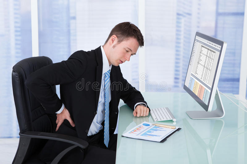 Businessman suffering from backache at computer desk stock photo