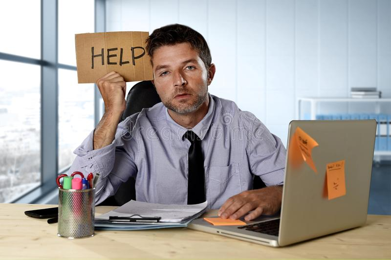 Businessman suffering stress working at computer desk holding sign asking for help looking tired exhausted. Young desperate businessman suffering stress working stock images
