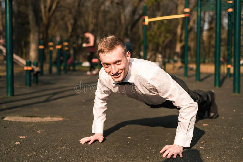 Businessman in a suit on the athletic fielddoing exercise. stock photo