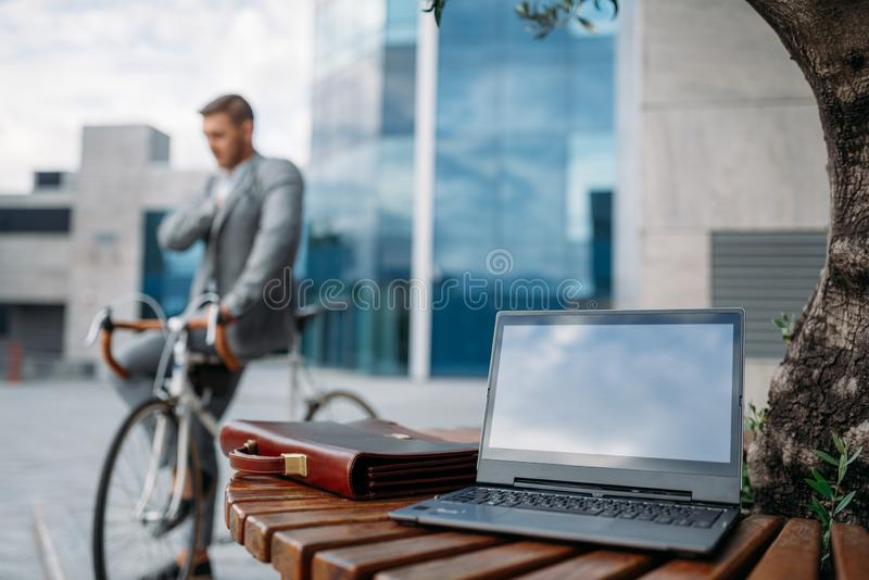 Businessman on bike, glass building on background stock images