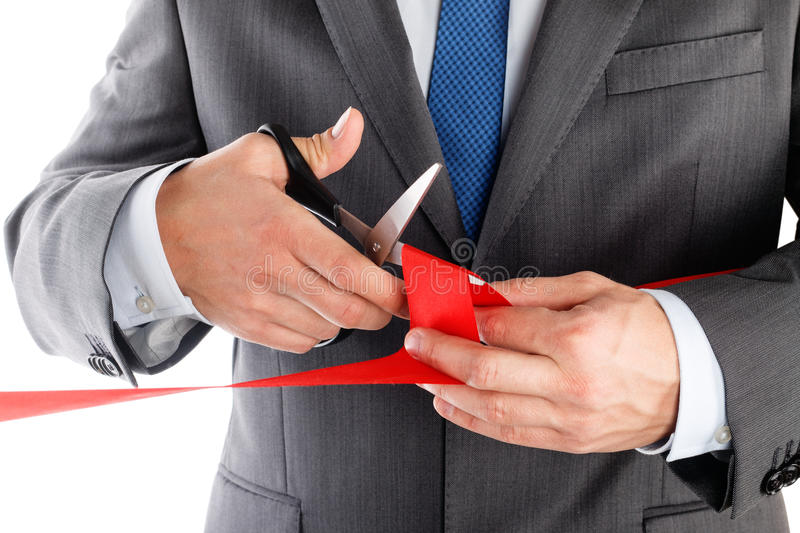 Businessman in suit cutting red ribbon with pair of scissors iso royalty free stock photos
