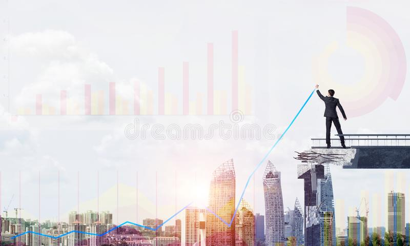 Businessman using modern media interface. Businessman in suit drawing graphs on modern statistical media interface while standing on broken bridge with royalty free stock photo
