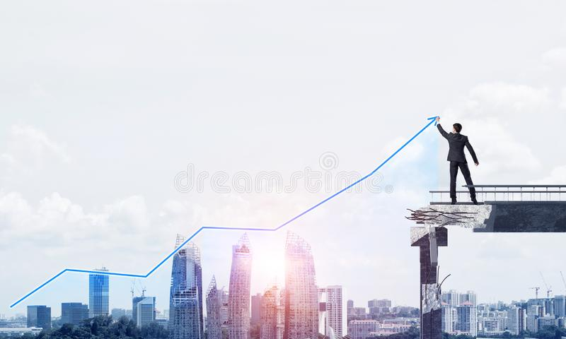 Businessman using modern media interface. Businessman in suit drawing graphs on modern statistical media interface while standing on broken bridge with royalty free stock photos
