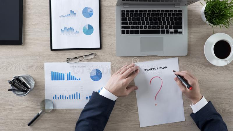 Businessman in suit drawing red question mark on startup plan, lack of ideas stock photos