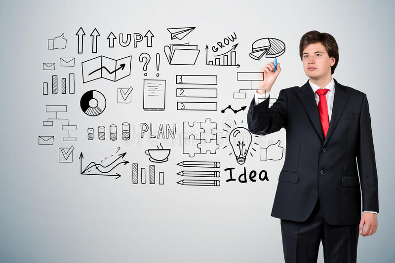 Businessman in a suit is drawing a startup idea sketch on a glas. Businessman in a suit with a red tie who is drawing a startup idea sketch on a glassboard near stock images