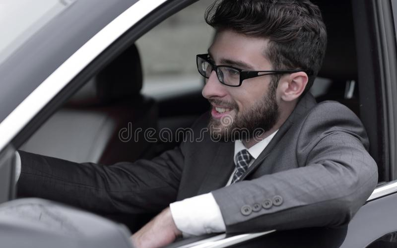 Businessman in suit driving his luxurious car. stock photo