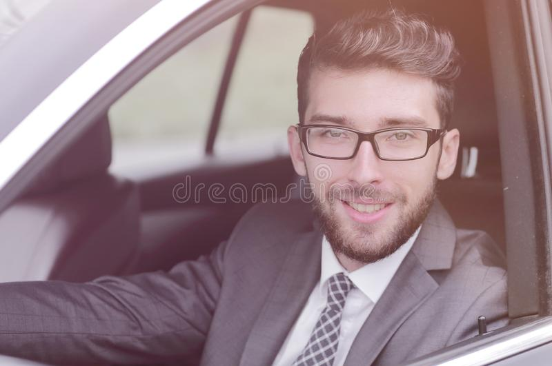 Businessman in suit driving his luxurious car. stock photography