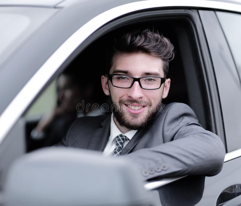Businessman in suit driving his luxurious car. royalty free stock image