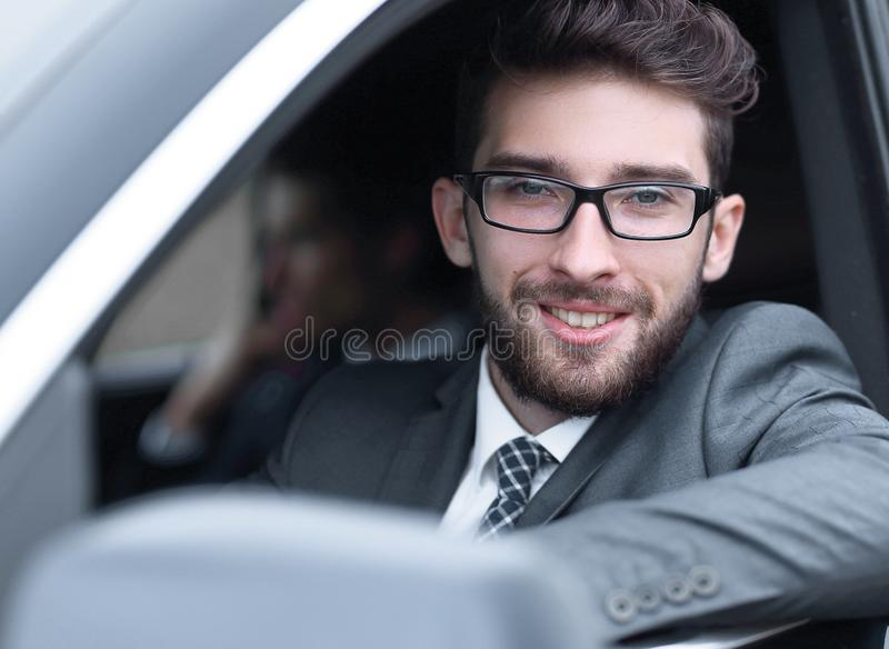 Businessman in suit driving his luxurious car. royalty free stock photos