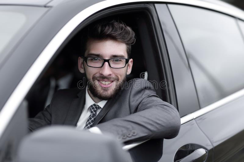 Businessman in suit driving his luxurious car. royalty free stock images