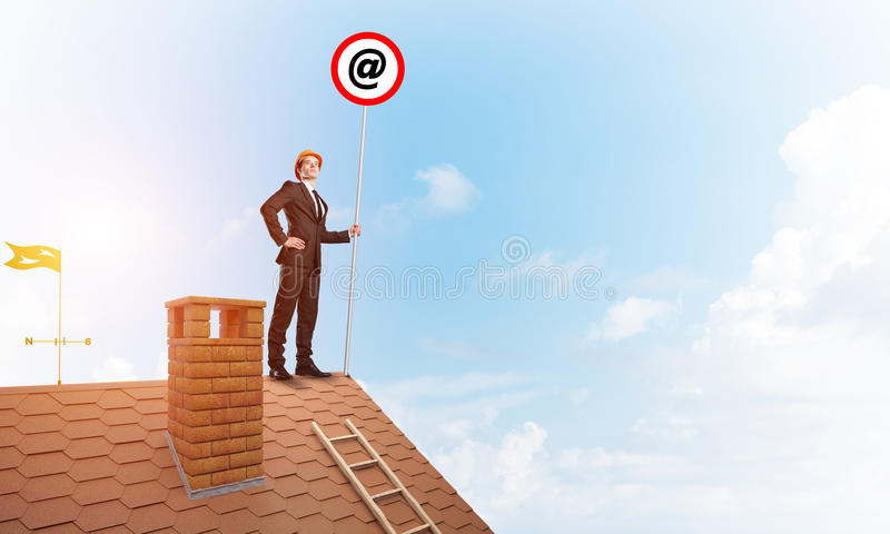Businessman in suit and helmet presenting email concept on signbaord. Mixed media. Young businessman on house roof with roadsign in hand. Mixed media stock image