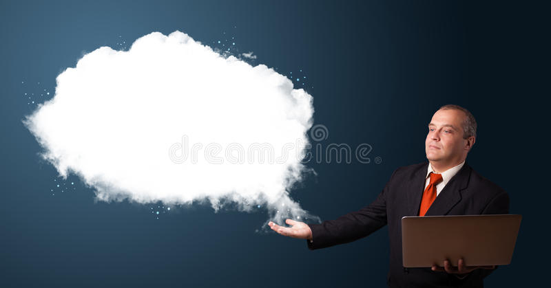Businessman in suit holding a laptop. And presenting abstract cloud copy space stock photo