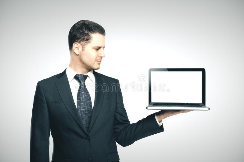 Businessman in suit holding laptop royalty free stock image