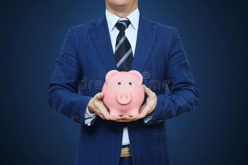 Businessman in suit is holding piggy bank. Businessman holding pig money box. Finance Savings concept stock photography
