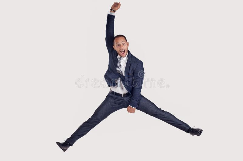 A businessman in a suit jumps for joy. stock image