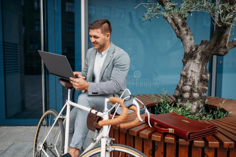 Businessman in suit with laptop and bike, downtown stock images