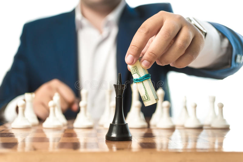 Businessman in suit make move with dollars in chess game. Closeup conceptual shot of businessman in suit make move with dollars in chess game royalty free stock photo