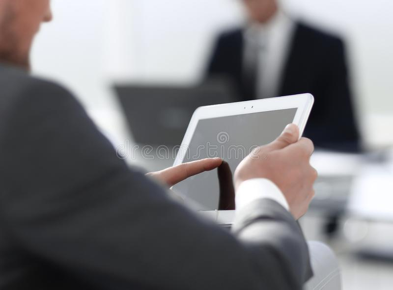 Businessman in suit in modern office using tablet royalty free stock image