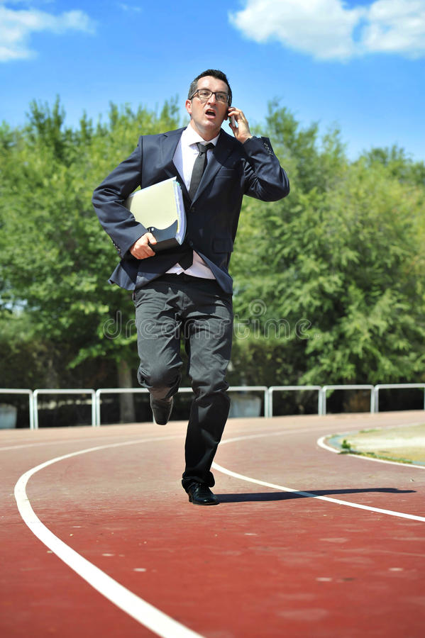 Businessman in suit and necktie carrying folder portfolio and files running in stress on athletic track talking on mobile phone. Looking tired and stressed in stock images