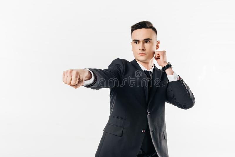 businessman in suit performing karate hit stock photos