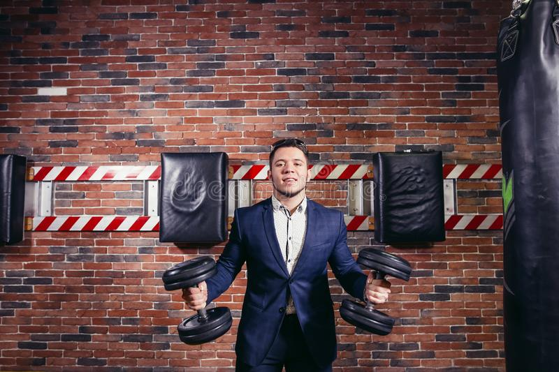 Businessman in suit raising dumbbell in office stock photos