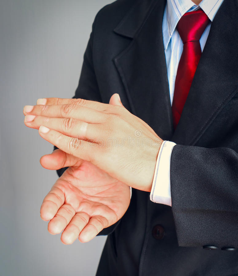 Businessman in suit with red tie showing gesture applaud. On gray background stock image