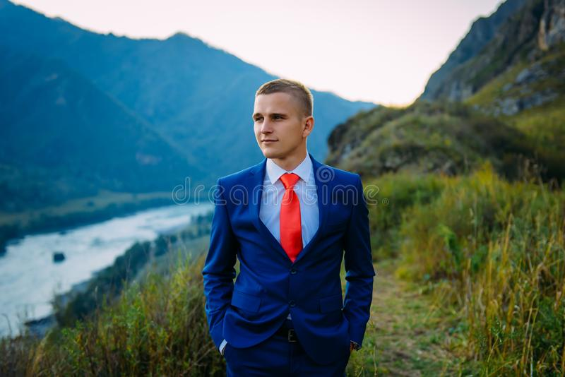 Businessman in a suit with red tie on the top of the world with background of mountains royalty free stock photo